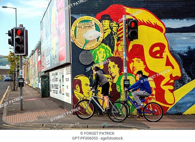 CHILDREN ON BICYCLES IN FRONT OF THE MURALS ON THE INTERNATIONAL WALL, DIVIS STREET, BELFAST, ULSTER, NORTHERN IRELAND