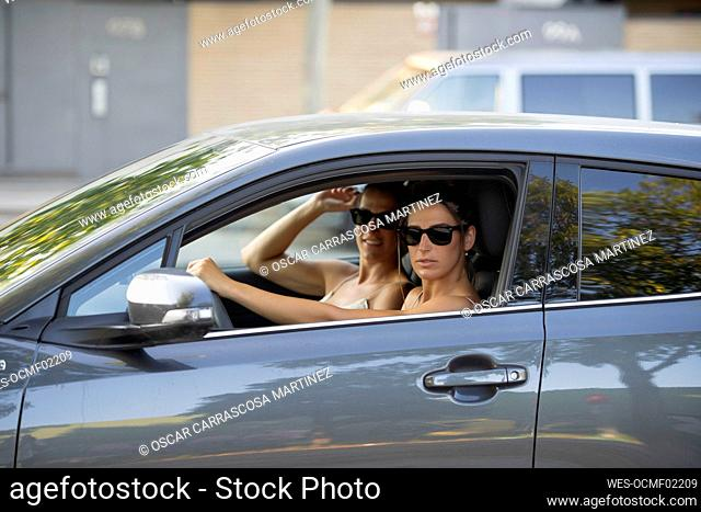 Mid adult twin sisters wearing sunglasses in car