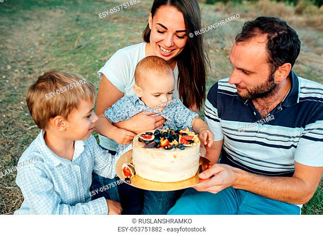A young family with two sons celebrating a birthday and eating a delicious cake