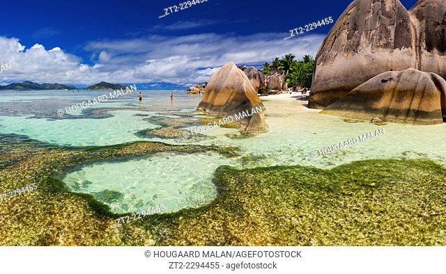Panoramic landscape view of tourists enjoying a sunny day on the famous Anse source d'Argent beach. La Digue Island, Seychelles