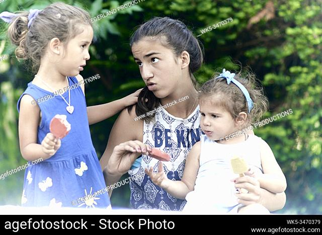 Young girl giving ice cream to her little sisters