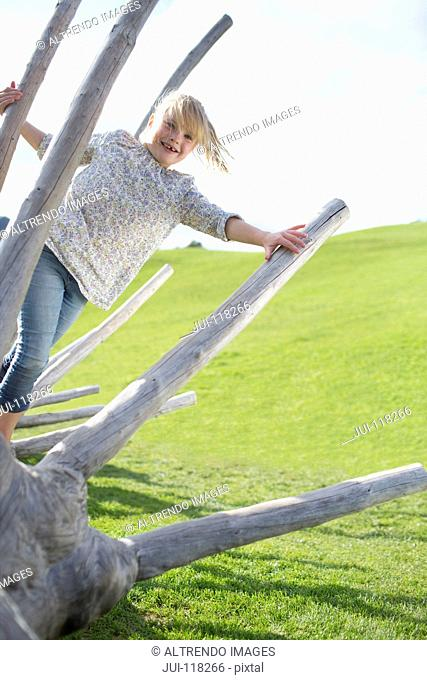 Young Girl Playing On Dead Tree In Countryside