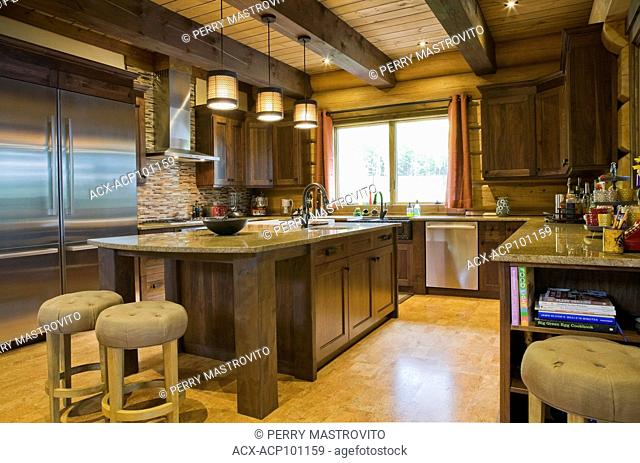 Brown stained pinewood island with granite countertop, sand coloured cloth upholstered barstools in kitchen with cork floor inside a luxurious Scandinavian log...