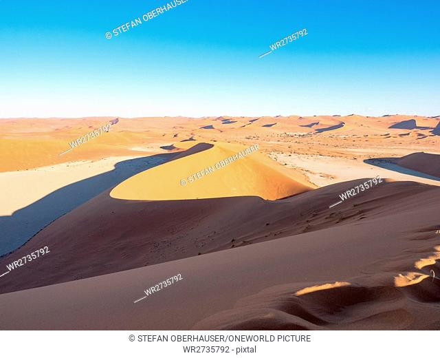 Namibia, Hardap, Sossusvlei, sand dune under sunlight, ascent of the Big Daddy Dune at sunrise, view over Dead Vvei (left)