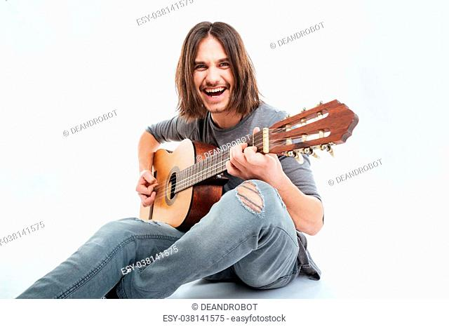 Cheerful handsome young man with long hair sitting and playing guitar over white background