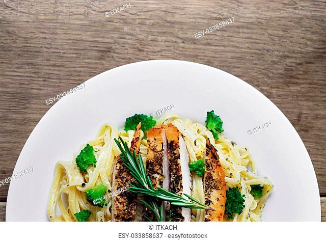 Pasta with fried chicken on the wooden table with vegetables