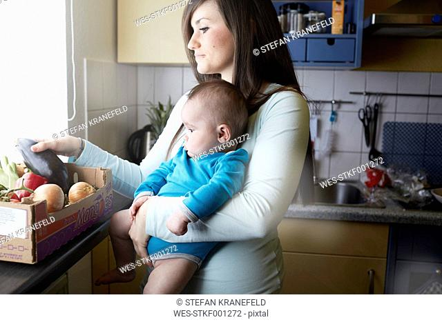 Young mother holding baby in kitchen