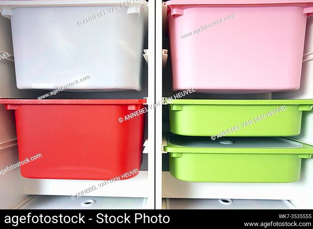 Stack of plastic storage boxes in different colors, sorting system arrangement close-up