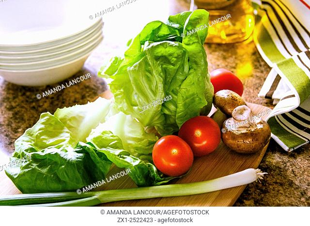 Lettuce, tomato and green onion, bamboo cutting board, cloth and oil on granite countertop with bowls in the background, backlit