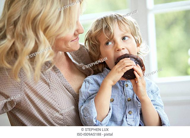Young boy seating chocolate muffin whilst his mother looks on