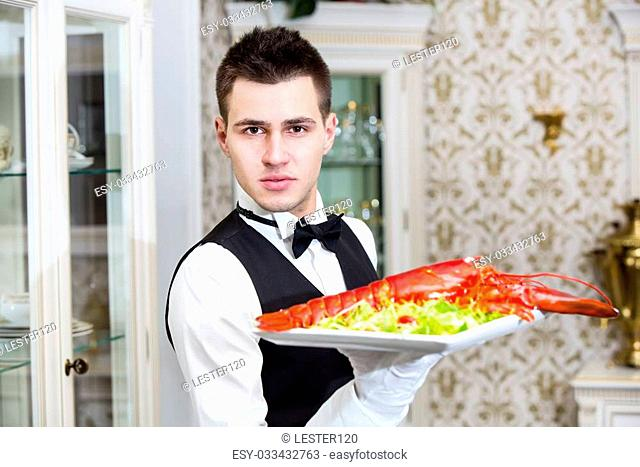 waiter with lobster on a plate in a restaurant