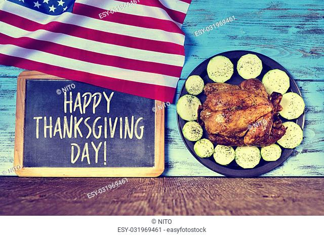 a flag of the United States, a chalkboard with the text happy thanksgiving day and a roast turkey in a tray with vegetables on a blue wooden rustic surface