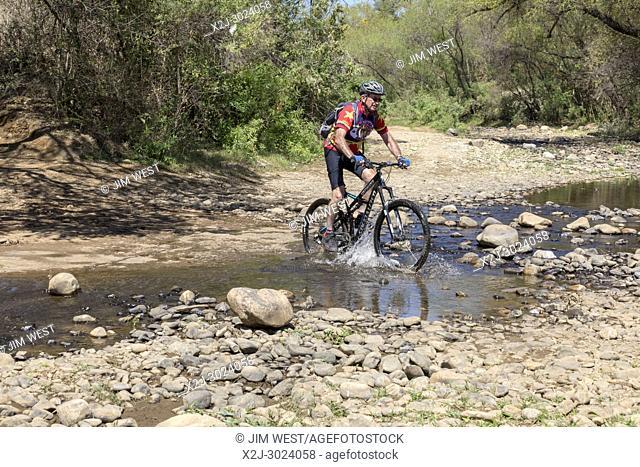 Oaxaca, Mexico - Larry Ginzkey rides his mountain bike across a stream in the West Etla Valley of rural Oaxaca