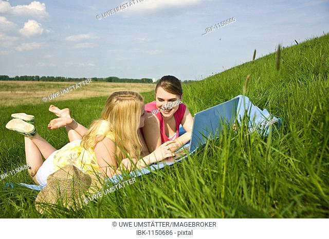 Two smiling girls using a laptop while lying on a blanket on a meadow