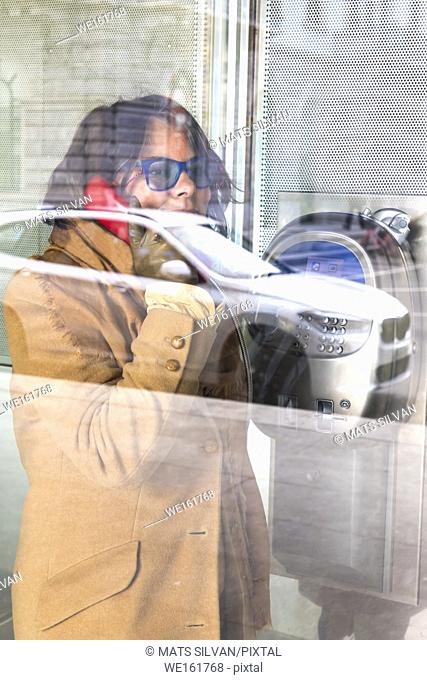 Woman Inside a Telephone Booth and Calling with Reflection