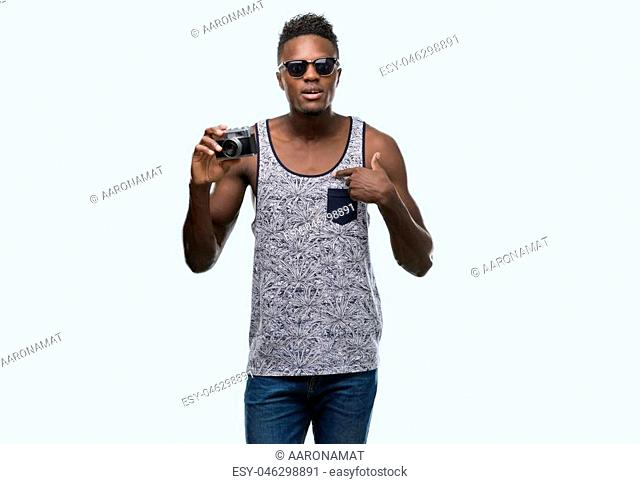 Young african american man holding vintage camera with surprise face pointing finger to himself