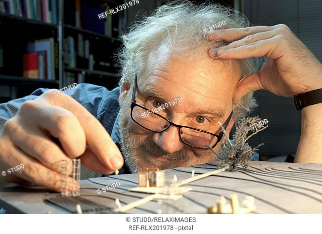 Portrait of happy mature man making architectural model of theater in workshop