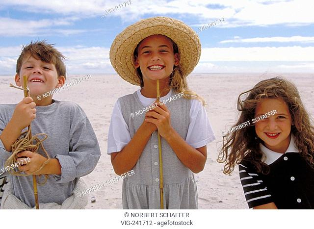 beach-scene, group of 3 children in the age of 7-10 years, 2 girls and 1 boy, stands laughing with stick and strawhat beside each other at the beach  - GERMANY