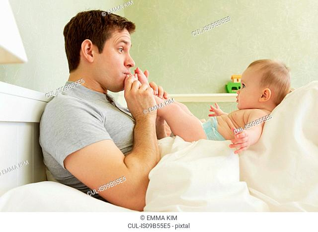 Mid adult man kissing baby daughter's feet in bed