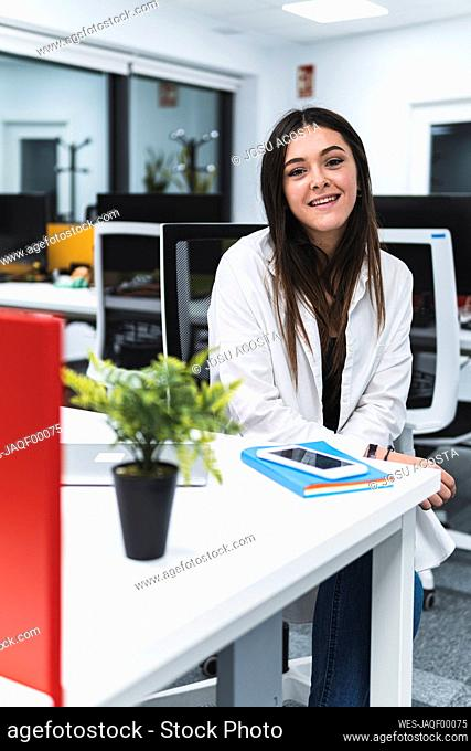 Happy young female entrepreneur on desk at work place
