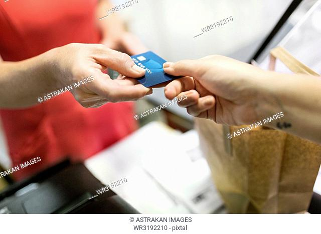 Close-up of customer giving credit card to sales clerk