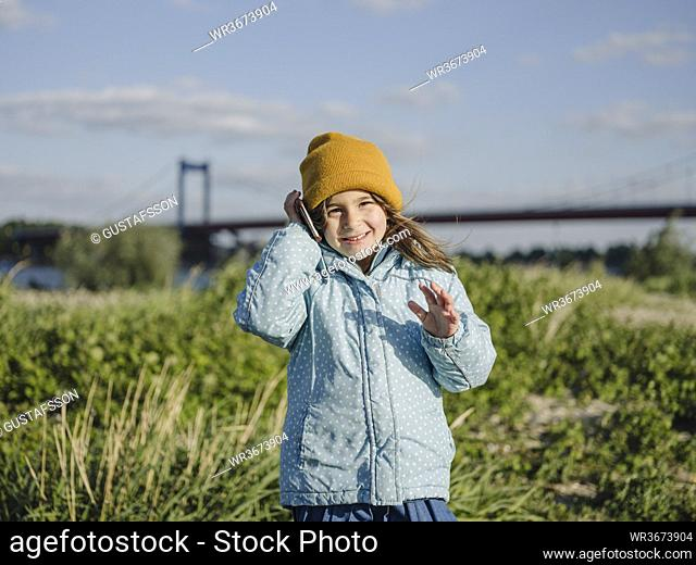 Cute smiling girl talking over smart phone while standing on land against sky