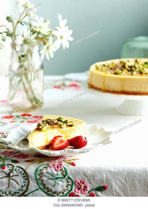 Slice of ricotta honey cheesecake and strawberries on plate