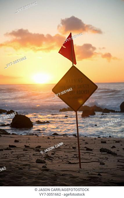 Sign says WARNING FOR YOUR SAFETY STAY OFF ROCKS and Hawaii pacific ocean taken in Oahu island, America. Oahu is known a tropical island located in Hawaii
