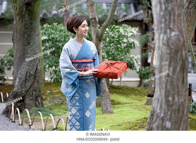 Young Japanese woman in kimono walking into Japanese garden