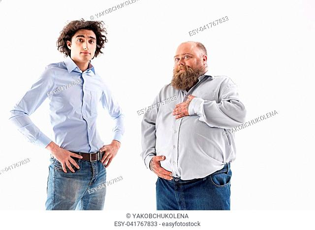 I am proud of my figure. Joyful fat man is touching his tummy with satisfaction and smiling. Slim guy is standing and looking forward with confidence