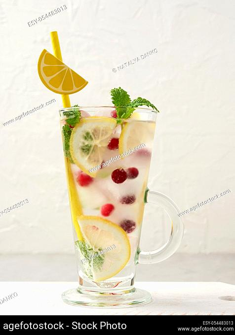 transparent glass with lemonade and pieces of ice, red berries and paper tubes, a refreshing summer drink
