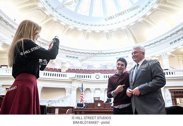 Caucasian couple taking photograph with politician in capitol building