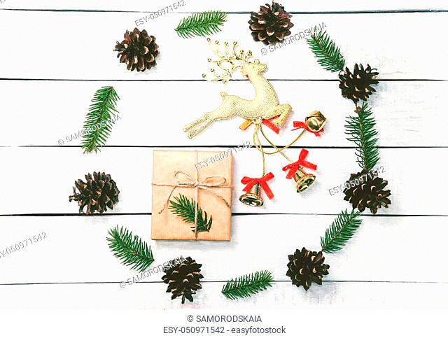 Christmas wreath made of pine cones and sprigs firon the white wooden background. Natural decor ornament for holiday card. Xmas card. Happy New Year
