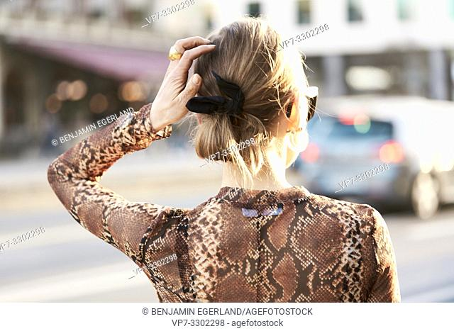 back view of fashionable woman at street in city, looking away, in Munich, Germany