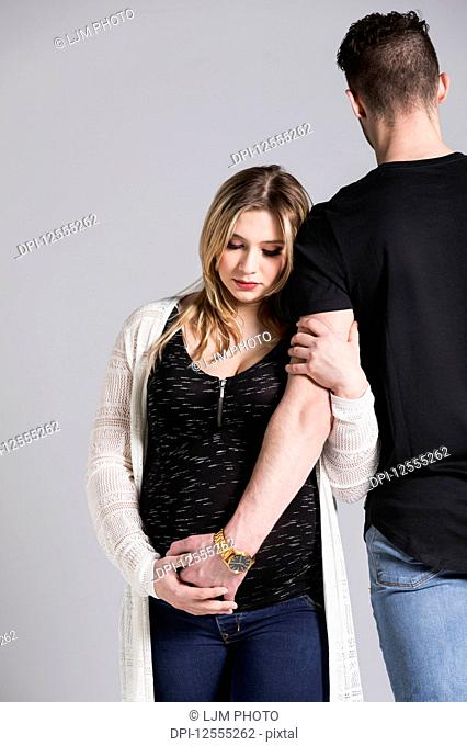 A young expectant couple with the father's hand on her belly in a studio on a light background: Edmonton, Alberta, Canada