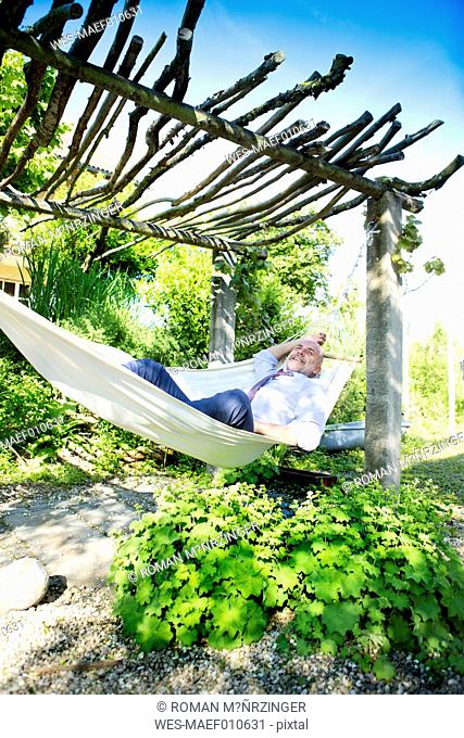 Businessman relaxing in hammock in a garden