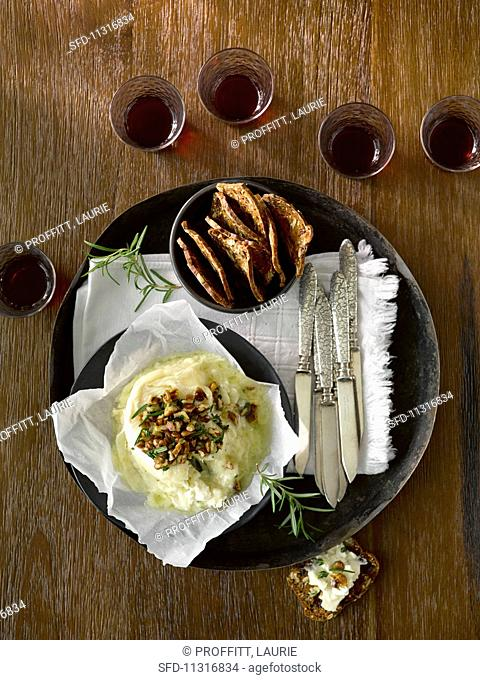 Brie topped with chopped nuts and rosemary served with fruit crisps red wine