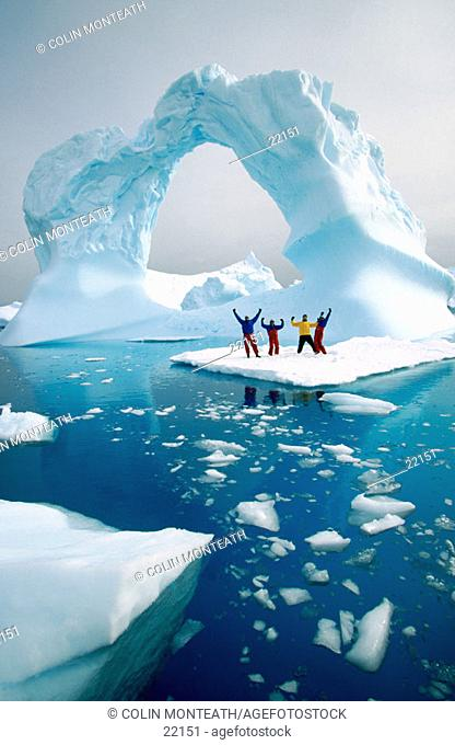 Men standing on a piece of floating ice. Nrear Petermann Island. Antarctic Peninsula