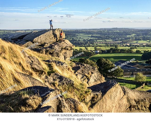 Climbers at Almscliff Crag with Arthington Viaduct in the distance near Harrogate North Yorkshire England