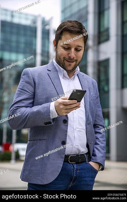 Businessman using smartphone Outdoors in front of Office Building. Texting, Sms, Internet Surfing, App, Communication. Corporate Business Concept