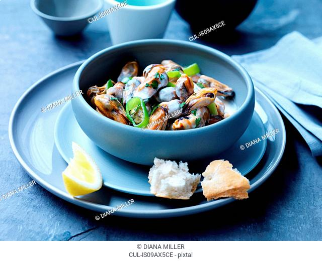Mussels, leeks, sauce and herbs in bowl with lemon slice