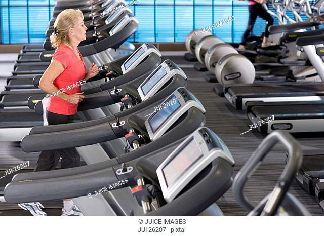 Senior woman running on treadmill in health club