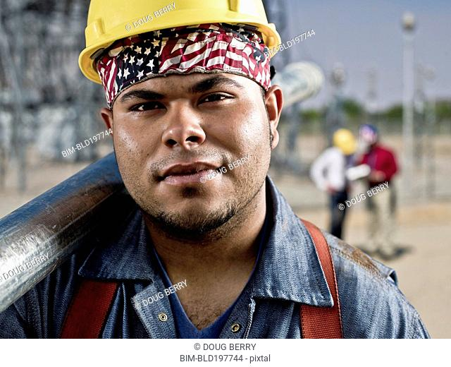 Mixed race construction worker carrying pipe