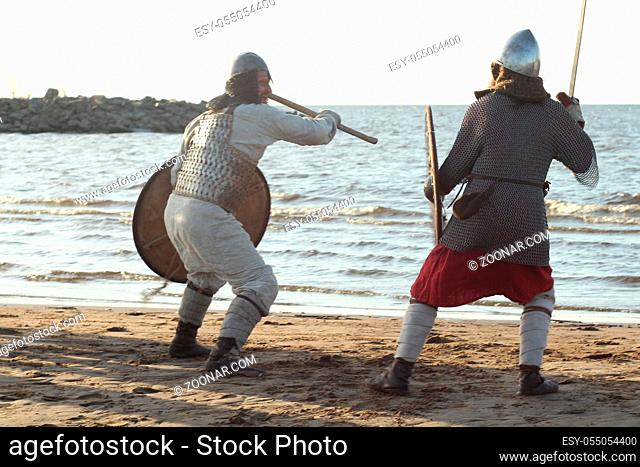 Two medieval Slav warriors are fighting with swords and shields on the beach