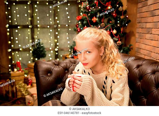 13 years old teen girl in warm sweater sitting on sofa in room decorated for Christmas holidays and drinking milk at home