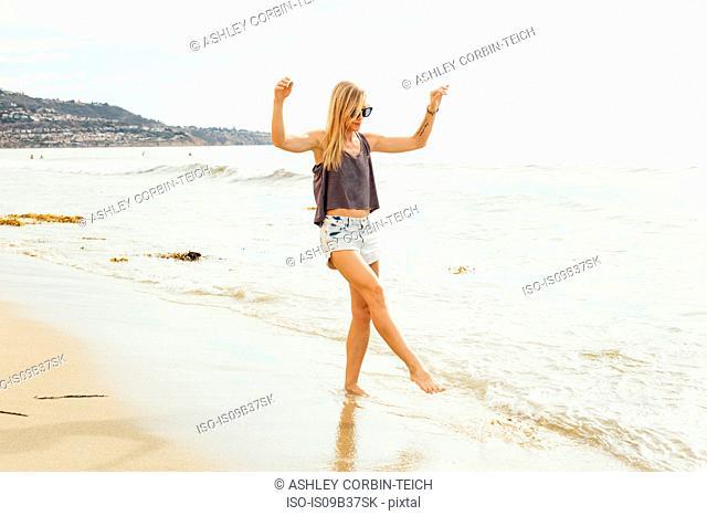 Woman on beach paddling on shoreline