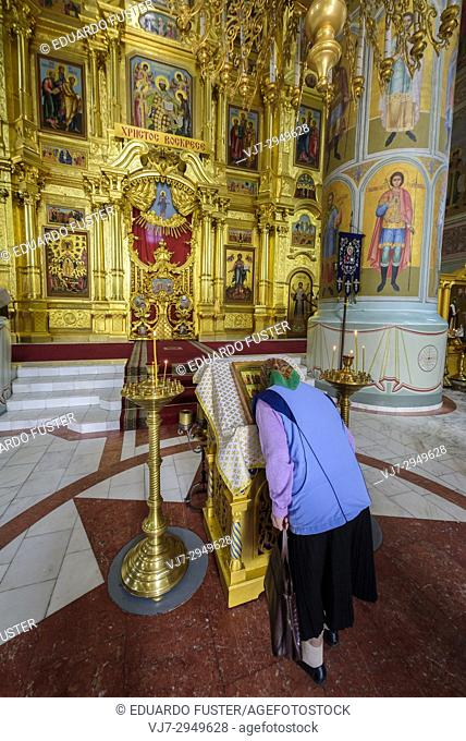 Russia, Kolomna. Woman praying in the interior of the Uspensky cathedral