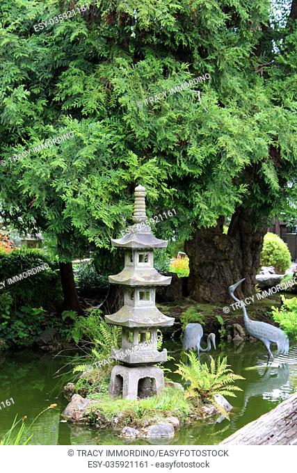 A landscaped Japanese garden with a Japanese stone lantern and bird statues in a pond in California, USA