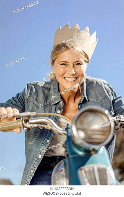 Smiling woman on vintage motorcycle wearing a crown