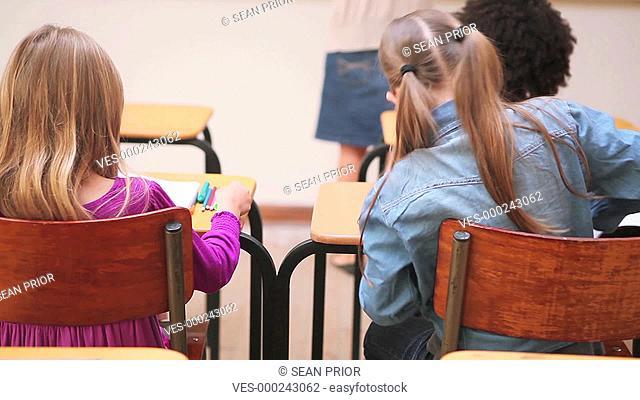 Kinder sitzen in einer Schulklasse mit dem R?cken zur Kamera. Zwei Kinder fl?stern sich etwas zu